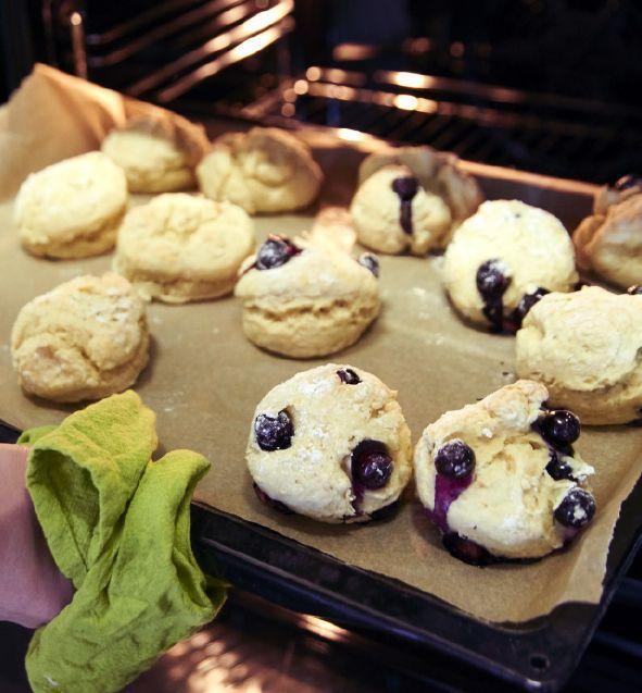 Muffins auf einem Backblech, das aus dem Backofen geholt wird